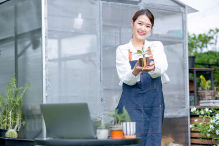 Beautiful Asian girl hold plant product and show to camera also stand in front of greenhouse workplace area
