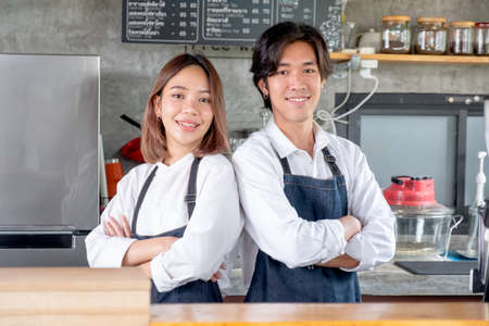 Two Asian barista or coffee maker man and woman stand with arm-crossed or confidence action also look to camera and smile in café shop. Concept of happy working with small business together.