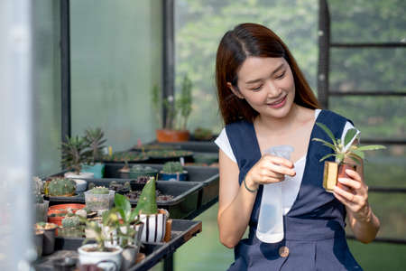 Beautiful Asian girl hold foggy bottle for spraying water to plant in small pot and sit in green garden in her house with sustainable and small business concept. Stock fotó