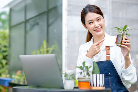 Beautiful Asian girl hold pot of plant and look at camera also pointing to pot stay with laptop on table in front green garden of her house.