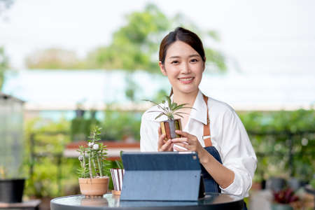 Beautiful Asian girl hold flora pot and look at camera with happy emotion. Sustainable with small business work involve with plant of flora concept.