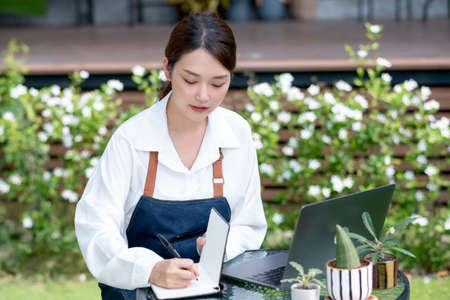 Beautiful Asian woman record the data into notebook in front of laptop and stay in home garden. Sustainable with small business relate to grow plant concept.
