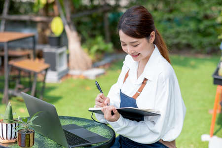 Beautiful Asian woman record the data into notebook in front of laptop and stay in home garden with happy emotion.