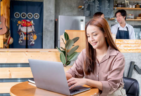 Beautiful Asian woman work with laptop in coffee shop and two barista or coffee maker work together in the back. Concept of small business and support by customer.