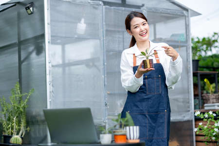 Beautiful Asian girl hold pot of plant and pointing to pot also look at camera with stand in front green garden of her house. Sustainable with small business relate to grow plant concept.