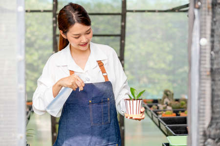 Beautiful Asian girl hold foggy bottle and spray water to plant in small pot and sit in green garden in her house. Sustainable with small business relate to grow plant concept.
