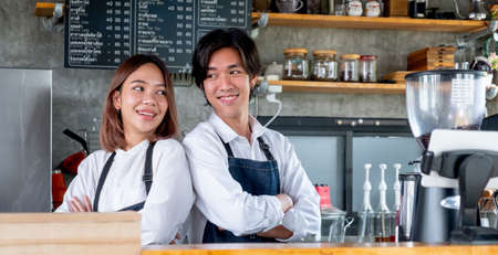 Two Asian barista or coffee maker man and woman stand with arm-crossed or confidence action also look to each other and smile in cafe shop. Concept of happy working with small business together.
