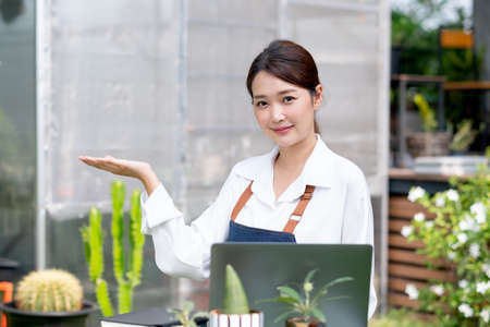 Beautiful Asian girl rest hand up look like present product and look at camera. Sustainable with small business work involve with plant of flora concept. Stock fotó
