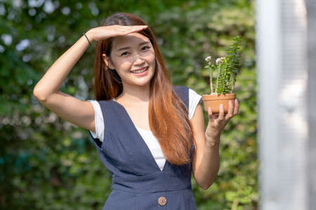 Beautiful Asian girl hold pot of plant with hand shading of light and stand near green house and smiling. Sustainable with small business relate to plant concept.