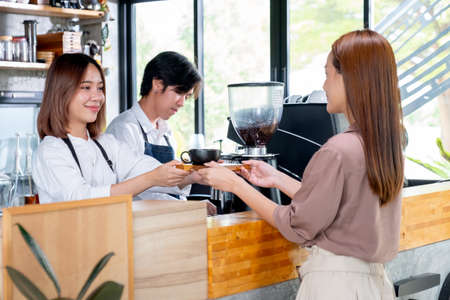 Beautiful Asian woman receive plate with coffee from barista or woman worker in coffee shop. Concept of small business and support by customer.