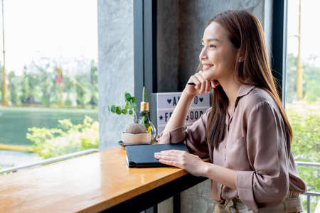 Beautiful Asian woman sit in corner of coffee shop with day light and look outside. She is smiling with happy emotion and think about her small business and sustainable activity. Stock fotó