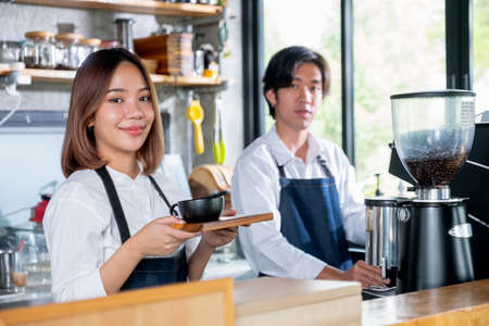 Barista woman or coffee maker hold plate with cup of coffee and look at camera in coffee shop and smiling. Concept of happy working with small business and sustainable together.