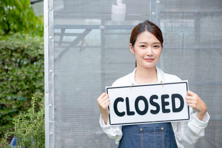 Beautiful Asian woman present banner with word closed in front of green house and sad emotion relate with close the business of sustainable activity.