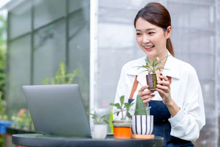 Beautiful Asian girl hold pot of plant and present to laptop on table in front green garden of her house look like online business.