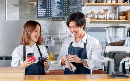 Two Asian barista or coffee maker man and woman work together in coffee shop. Concept of happy working with small business together.