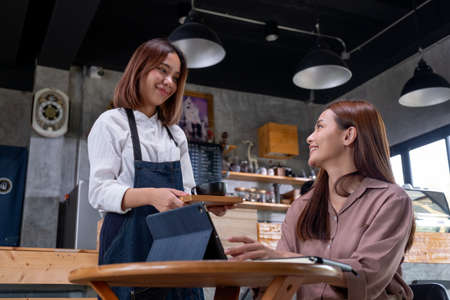 Beautiful working woman sit in coffee shop and get service from barista woman and they smile to each other with happy emotion.