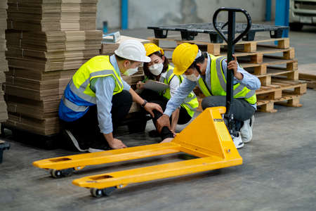 Factory worker woman was help and take care by coworker men after accident on her leg by hydraulic cart in warehouse workplace area. Stock Photo