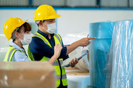 Two factory worker man and woman with safety uniform work together in warehouse by checking the product and discuss during process of collection and transfer in industrial business. Stock Photo