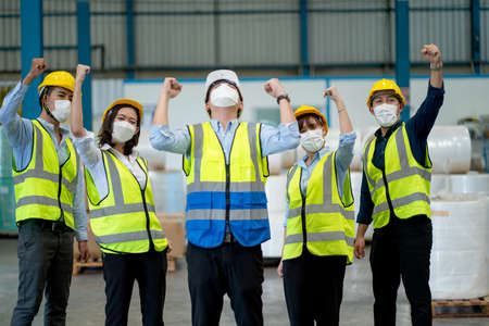 Group of warehouse worker with uniform and hygiene express happiness emotion and stand together in workplace. Stock Photo
