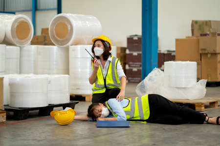 Factory worker woman use walkie talkie ask help to support and save her coworker who faint and lie down on floor during work in warehouse workplace area.