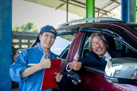 Asian automotive technician stand and show thumbs up with his customer who sit in car and smiling in workplace area after finish fix the problem of car. Stock Photo