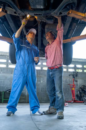 Wide shot of automotive technician discuss with senior customer during show the problem of car under the car in workplace. Stock Photo