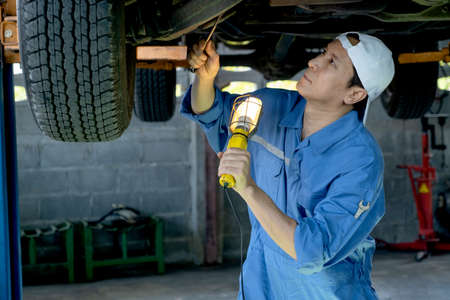 Asian technician or garage worker stand and use lantern to guide for check and also use wrench to fix  problem in workplace area.