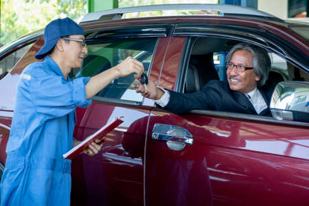 Asian automotive worker give car key back to senior customer who sit in car and smile after finish fix problem of his car in workplace shop.