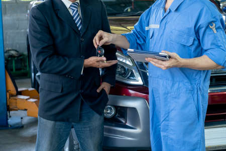 Close up shot automotive technician give car key back to customer after finish fix the problem of car in workplace area. Stock Photo