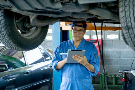 Asian automotive technician hold tablet and check data under car in mechanic shop.