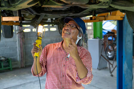 Manager of automotive shop hold light and wrench also look at under car with smiling during look to the position for fixing problem. Stock Photo