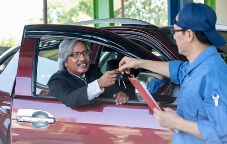 Automotive technician return the key back to senior customer sit in car and smiling after finish fix the problem of car.