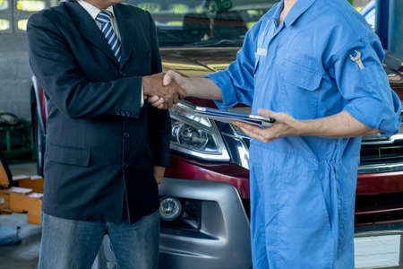 Automotive technician shake hands with customer in front of car in workplace after finish to fix problem. Stock Photo