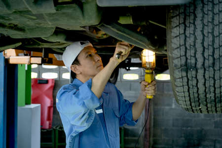 Technician or garage worker stand and work under the car and use lantern to guide for check and fix the problem in workplace area.