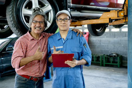 Customer heck the neck of automotive technician with smiling and look at camera also show thumbs up.