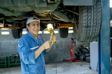 Asian automotive technician hold light stay under car and smile also look at camera. Stock Photo