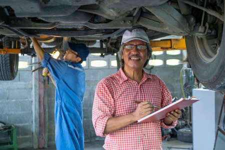 Manager of automotive mechanic shop hold document, smile and look at camera while technician work under car in the background. Stock Photo