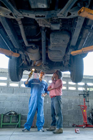 Asian automotive technician and senior customer discuss together under and in part of front car in workplace area. Stock Photo