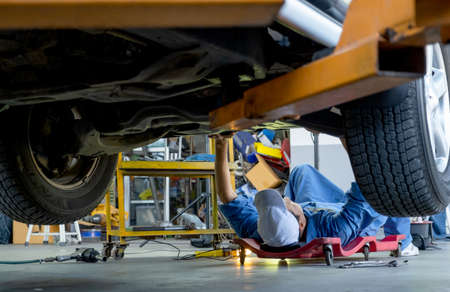 Lower view under car garage worker or technician lie down and check problem in workplace area. Garage management system support employee for working with happiness concept.