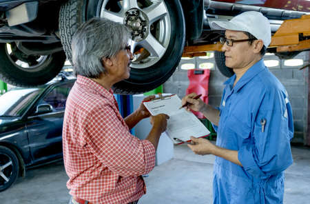 Asian automotive technician discuss about contact form to senior customer during service to fix problem for his car in workplace. Stock Photo