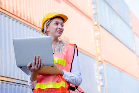 Foreman or cargo container technician or worker hold laptop and look to her left side during work in workplace.
