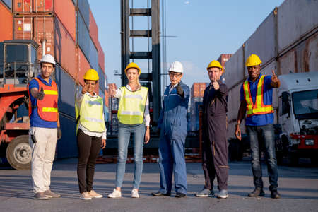 Group of foreman and cargo container workers or technician stand in row and show thumbs up to camera for symbol of successful in delivery and transport system business.