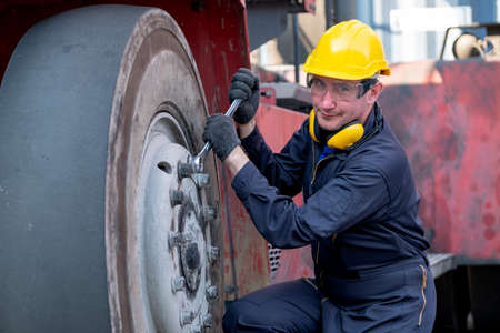Cargo container technician or worker use wrench to fix problem about truck tire and also look at camera during work in workplace area.
