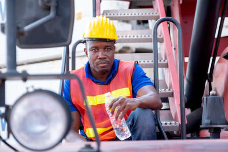 Foreman or cargo container worker with professional uniform hold water bottle and look at camera during sit on crane and relax after finish his work in workplace.