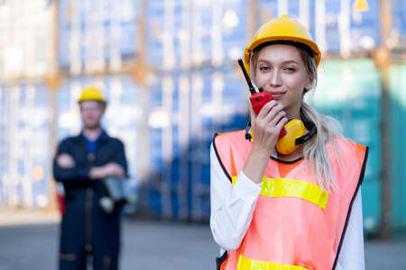 Cargo container woman worker or foreman use walkie to talk with her team and other technician stand with arm crossed in the back of workplace. Stock Photo