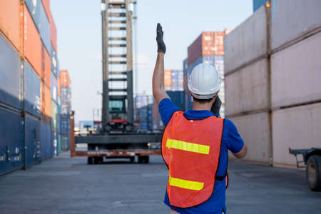 Back of foreman or cargo container worker give hand signal to crane movement in workplace area. Concept of teamwork support for delivery factory business system.