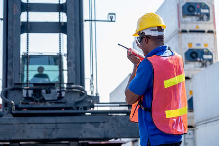 African American foreman use walkie talkie to communicate with crane driver during work together in cargo container workplace.