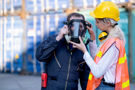 Cargo container woman worker help technician to wear gas protective mask and prepare for manage the problem in workplace area.