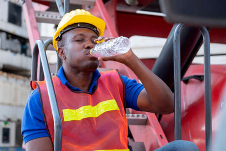 African American foreman or container worker drink water with close his eye and sit to relax on crane truck.