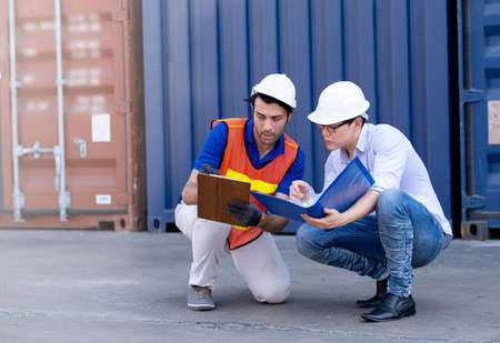 Foreman and container worker sit and discuss together about data in their document.